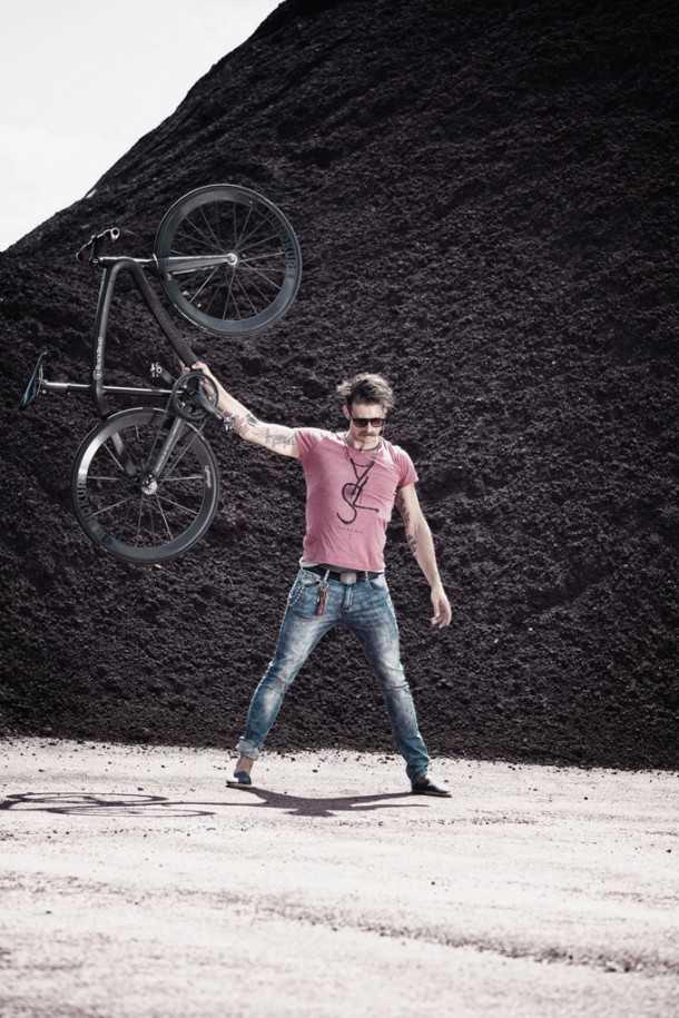 הנה גבר גרמני חסון המדגים את משקל הנוצה של האופניים.  צילום: Munich Composites
