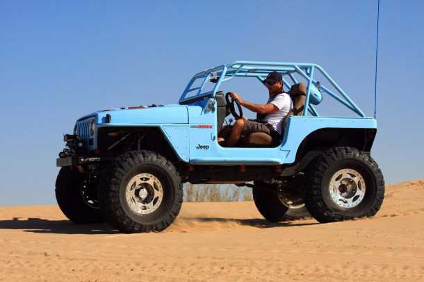 מבחן רכב ג'יפ רנגלר TJ משופר. המקור של המנוע הוא מקאדילק, כך שיהיה ראוי שגם הצבע הכחול הוא גוון של קאדילק. בסיס הגלגלים נמתח כמעה. צילום: רמי גלבוע