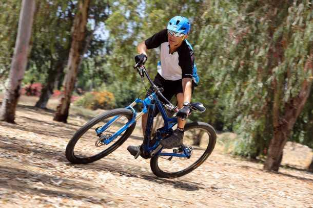 פניות על אופניים. מצויין! דיווש אגרסיבי בעמידה, מושב נמוך ולא מפריע ואפילו בפניה שטוחה כזו ודלת אחיזה אפשר לטוס במהירות. שימו לב למבט, למשקל על הדוושה החיצונית ולהטיה העמוקה הנחוצה כדי לגרום ל-אופניים עם גלגלי 29 אינץ' לפנות. צילום: תומר פדר