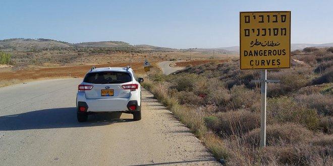 סובארו לבנה עומדת על כביש ליד שטח סיבובים מסוכנים